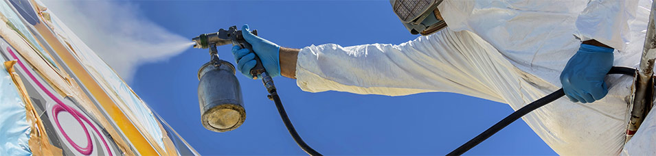 photo of man spary coating an aircraft